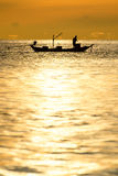 Silhouette of fishermen in the boat on sea with yellow and orange sun in the background Royalty Free Stock Images