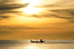 Silhouette of fishermen in the boat on sea with yellow and orange sun in the background. Thailand Stock Photo