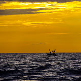 Silhouette of fishermen with  boats fishing Stock Images