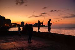 Silhouette of fishermen and the city skyline in Havana. At sunset Stock Photography