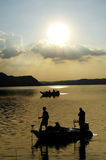 Silhouette of fishermen on dam water Royalty Free Stock Images