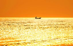 Silhouette of Fishermen on a fishing boat in the sea. And evening golden light. stock photo