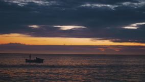 Silhouette of Fishermen with his Boat in Ocean stock footage
