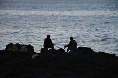 Silhouette of fishermen on rocks, Havana, Cuba Royalty Free Stock Photos