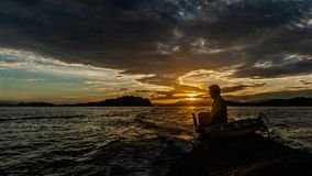 Silhouette of fishermen sailing boat at Ko Chang Island Ranong Province Thailand. Fishermen sailing boat in the sea at Ko Chang Island Ranong Province Thailand stock image