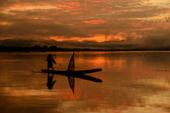 Silhouette of fishermen sailing on the sunrise. Royalty Free Stock Image