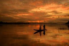 Silhouette of fishermen sailing on the sunrise. Stock Photos