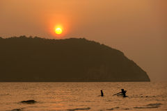Silhouette of fishermen with  sunset in the background Royalty Free Stock Images