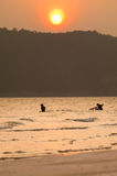 Silhouette of fishermen with  sunset in the background Stock Photography