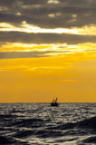 Silhouette of fishermen with thier boats fishing when the sunris Stock Photo
