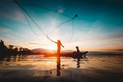 Silhouette of fishermen using nets to catch fish. At the lake in the morning royalty free stock image