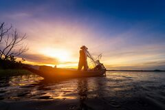 Silhouette of fishermen using nets to catch fish at the lake