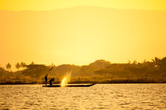 Silhouette of fishermen. With yellow and orange background Stock Photo