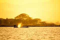 Silhouette of fishermen. With yellow and orange background Stock Images