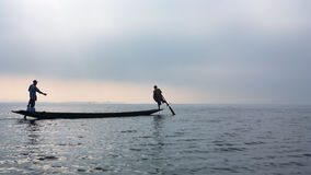 Silhouette of fishers paddling by legs on Inle lake, Myanmar stock images