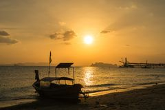 Silhouette fishing boat on the beach and island during sunrise.  Royalty Free Stock Image