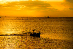 Silhouette of fishing boat and fishermen in sea Stock Image