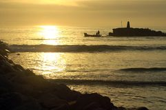 Silhouette of a fishing boat leaving the harbour Stock Photography