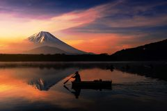 Silhouette  fishing boat with Mt. Fuji view. Silhouette man on fishing boat propelling oars on Shoji lake with beauty Mt. Fuji or Fujisan and mist view  by Stock Photos