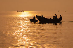 Silhouette of fishing boat return to port Stock Photos
