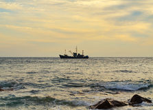 Silhouette fishing boat in sea Stock Photos