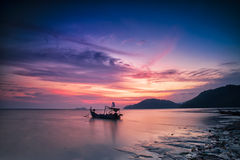 Silhouette of a Fishing Boat at sunset in Holiday Concept. Stock Images