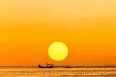 Silhouette fishing boat on sunset Stock Photos