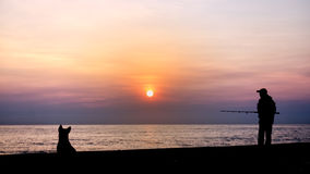 Silhouette of the fishing and dog Stock Photography