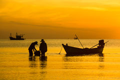 Silhouette of fishing and fisherman boat at the Sunrise in thailand Royalty Free Stock Photo