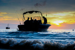 Silhouette of fishing man and a boate on sunlise at similand, Th Stock Photos