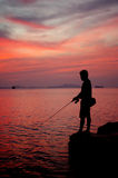 Silhouette of fishing man Stock Photos