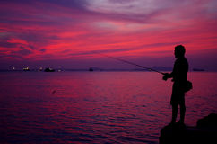 Silhouette of fishing man beside the sea Royalty Free Stock Images