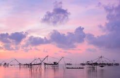 Silhouette fishing net trap at sunrise seascape Stock Photos