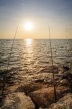Silhouette fishing rod on a beach. Stock Images