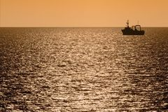 Silhouette of fishing trawler at dusk stock image
