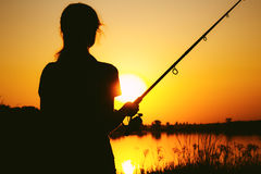 Silhouette of a fishing woman on the river bank at sunset Royalty Free Stock Photography