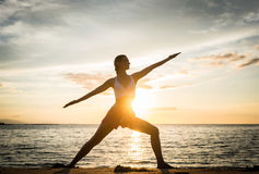 Silhouette of a fit woman practicing the warrior yoga pose again Stock Photo