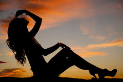 Silhouette of a fit woman sit hand over head Stock Images