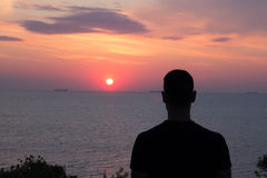 Silhouette of fit young man watching wunset or sunrise in the sea or ocean Stock Photos
