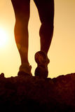 Silhouette  of fitness girl  legs running at sunset Stock Photos