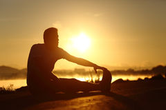 Silhouette of a fitness man stretching at sunset Royalty Free Stock Photo
