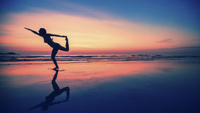 Silhouette of fitness woman on the beach. Yoga. stock images