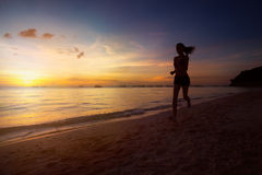 Silhouette of fitness woman jogging at sunrise. Silhouette of healthy lifestyle fitness woman jogging at sunrise/sunset beach Royalty Free Stock Images