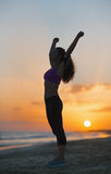Silhouette of fitness young woman rejoicing on beach at dusk. Silhouette of fitness young woman  in sportswear rejoicing on beach at dusk Stock Photo