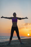 Silhouette of fitness young woman rejoicing on beach at dusk Royalty Free Stock Photo
