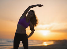 Silhouette of fitness young woman stretching on beach at dusk Stock Image