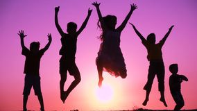 Silhouette of five kids family jumping at sunrise