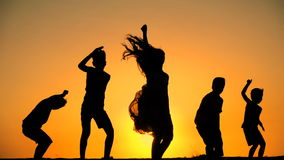 Silhouette of five kids jumping against sunset stock video