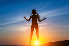 Silhouette of flexible dancing girl on the sea coast. Silhouette of flexible dancing girl on the sea coast during a amazing sunset Stock Photos