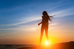 Silhouette of flexible dancing girl on the sea coast. During a sunset Stock Photography